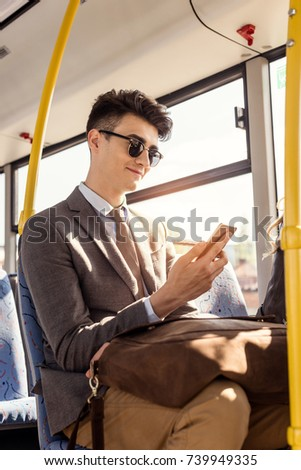 portrait of young man in sunglasses using smartphone in city bus