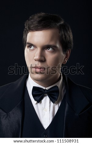 portrait of young man in tuxedo isolated on dark background - stock photo