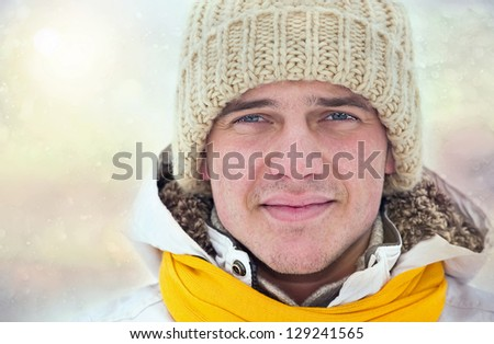 portrait of young man in winter landscape - stock photo