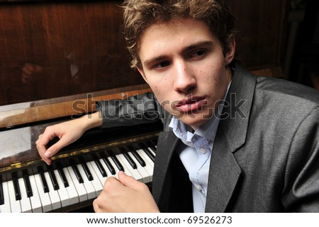 Portrait of young man indoor at his apartment in evening playing piano - stock photo