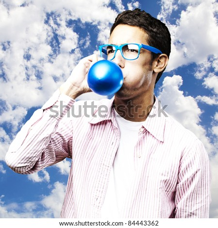 portrait of young man inflating a blue balloon against a sky background - stock photo