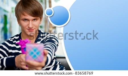 Portrait of young man inside shopping mall sitting relaxed on couch, holding box and preparing to make his couple a gift. Blank balloon with lots of copyspace for your text and logo