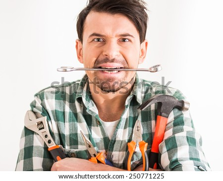 Portrait of young man is doing repair at home with tools. - stock photo