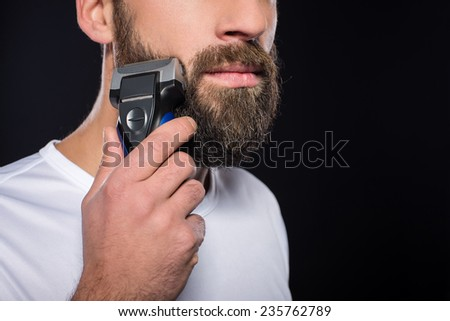 Portrait of young man is shaving his beard. Black background. - stock photo