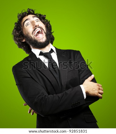 portrait of young man laughing against a green background