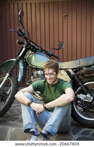Portrait of young man leaning on motorbike - stock photo