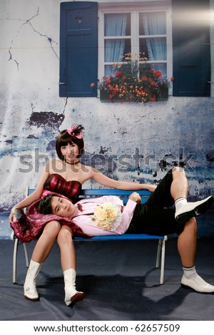 Portrait of young man lie his head on girl knee and looking to you - stock photo