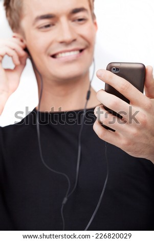 Portrait of young man listening music on cell phone. closeup on guy in earphones isolated on white background.  - stock photo