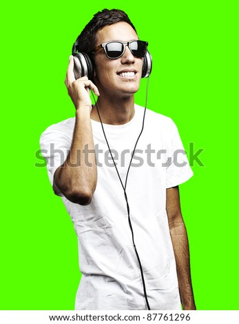 portrait of young man listening to music against a removable chroma key background - stock photo