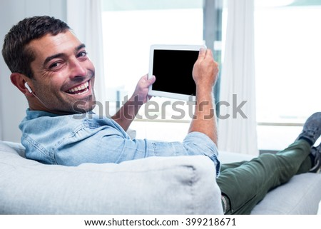 Portrait of young man listening to music while using tablet in living room