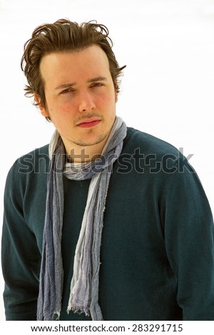 Portrait of young man looking at camera, with sweater and blue scarf around his neck, isolated on snowy background - stock photo