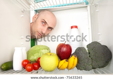 Portrait of young man looking at different healthy food inside refrigerator.