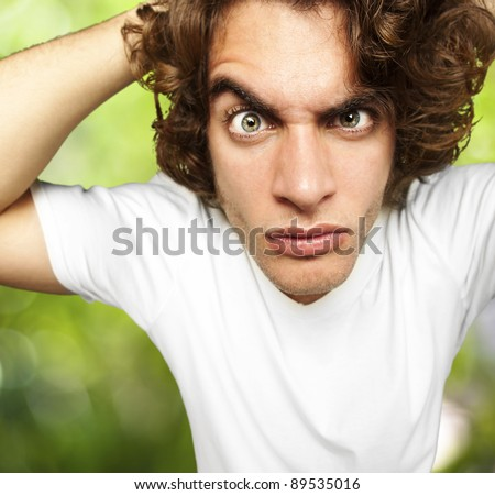 portrait of young man looking confused against a nature background - stock photo