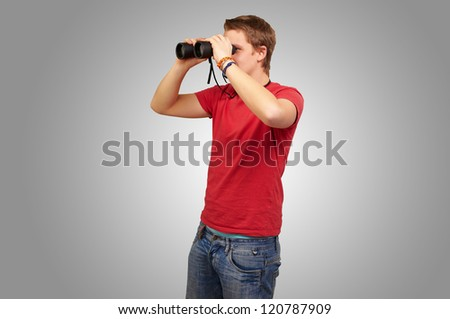 portrait of young man looking through a binoculars over grey background