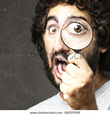 portrait of young man looking through a magnifying glass against a grunge wall - stock photo