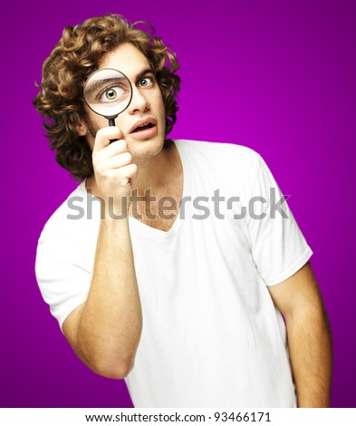 portrait of young man looking through a magnifying glass against a pink background - stock photo