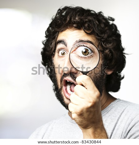 portrait of young man looking through a magnifying glass in a living room