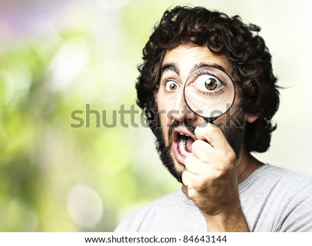 portrait of young man looking through a magnifying glass in the park