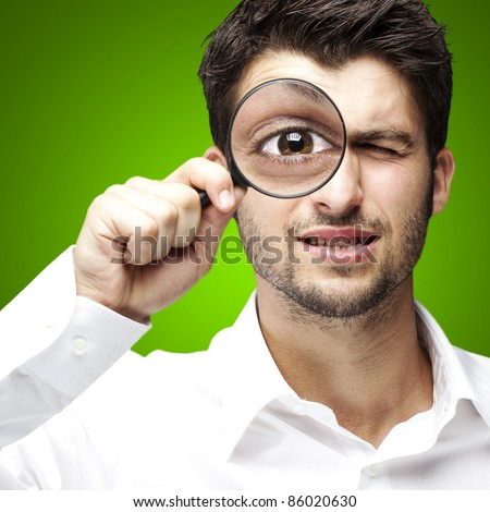 portrait of young man looking through a magnifying glass over green background - stock photo
