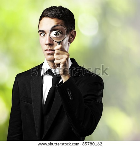 portrait of young man looking trough a magnifying glass in a park