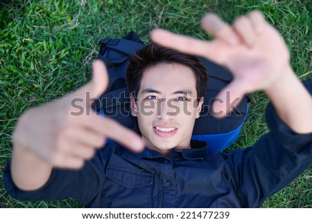 Portrait of young man lying on the green grass doing a frame with his fingers  - stock photo
