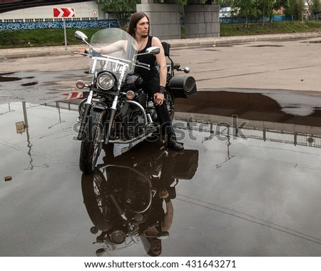Portrait of young man on black motorcycle with puddle reflection