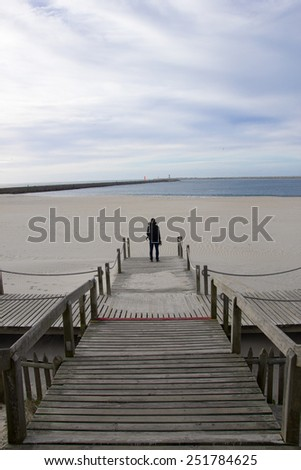 Portrait of young man on the beach looking at the ocean. back view
