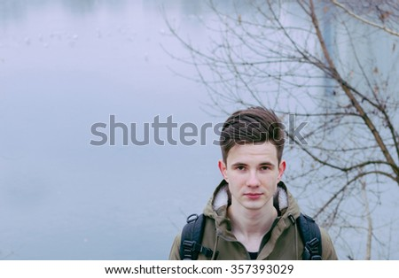 Portrait of young man on the city river in autumn time, photo with place for text and other - stock photo