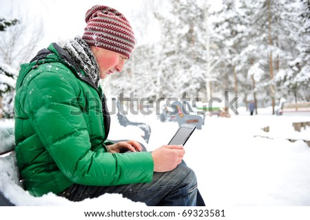 Portrait of young man outdoor in winter park wearing bright clothes working with his netbook and enjoying free wireless internet connection - stock photo