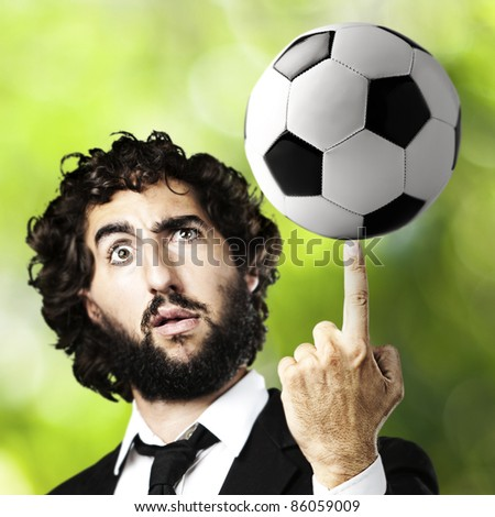 portrait of young man playing with a soccer ball against a park background - stock photo