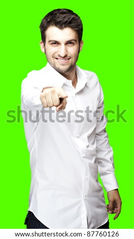 portrait of young man pointing against a removable chroma key background