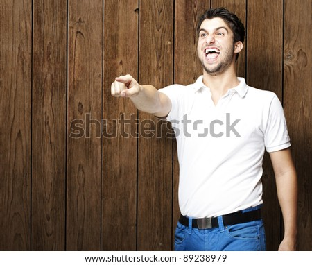portrait of young man pointing with finger against a wooden wall