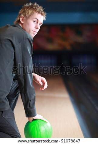 Portrait of young man prepared on bowling lane - stock photo