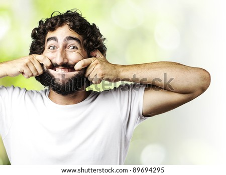 portrait of young man pulling his mouth smiling against a abstract background - stock photo