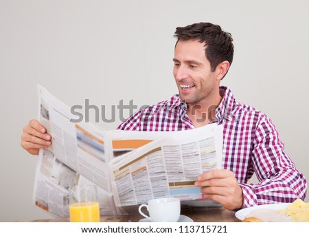 Portrait Of Young Man Reading Newspaper At Breakfast, Indoors - stock photo
