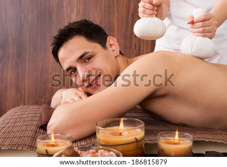 Portrait of young man receiving massage with stamps in spa - stock photo