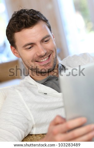 Portrait of young man relaxing in sofa with electronic tablet - stock photo