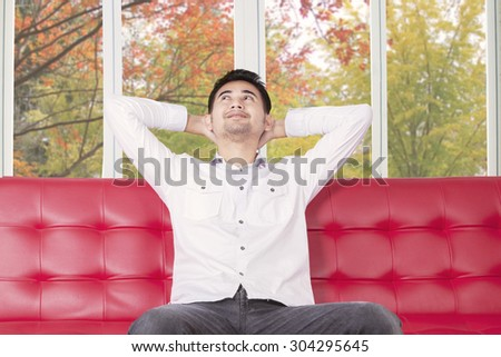 Portrait of young man relaxing on sofa while thinking something and looks happy, shot with autumn background on the window - stock photo