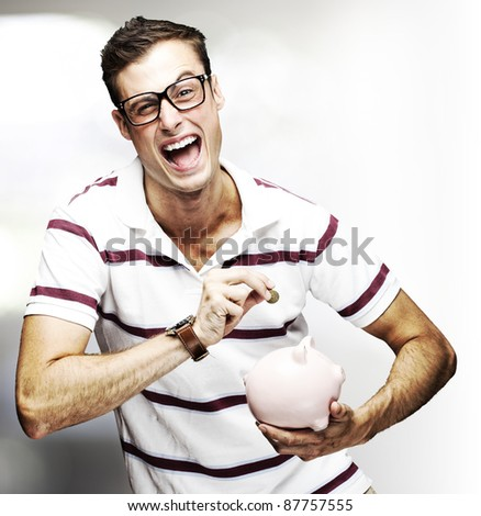 portrait of young man saving coins in piggy bank indoor