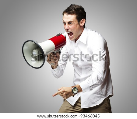portrait of young man screaming with megaphone against a grey background - stock photo