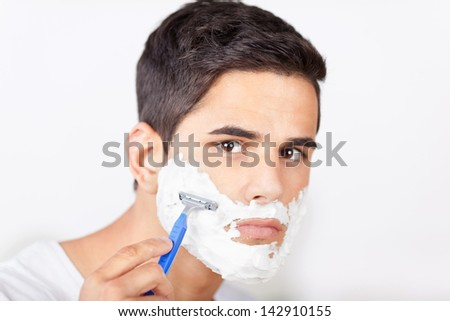 Portrait of young man shaving - stock photo