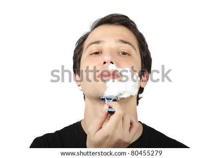 portrait of young man shaving himself - stock photo
