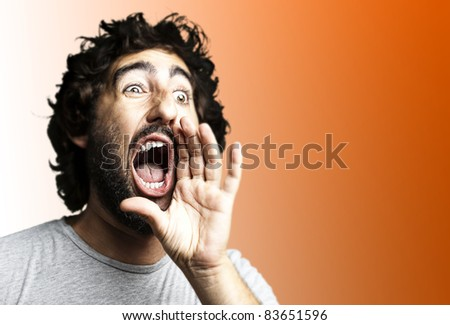 portrait of young man shouting against a blue background - stock photo