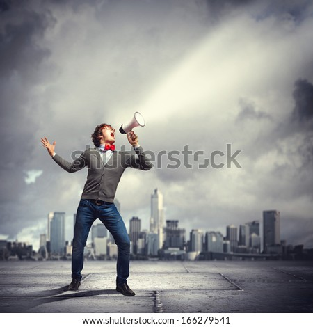 Portrait of young man shouting loudly using megaphone - stock photo