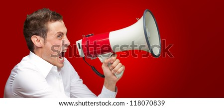 Portrait Of Young Man Shouting On Megaphone Isolated On Red Background