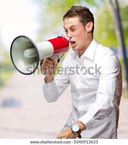 Portrait Of Young Man Shouting On Megaphone, Outdoor