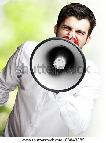 portrait of young man shouting using megaphone against a nature background