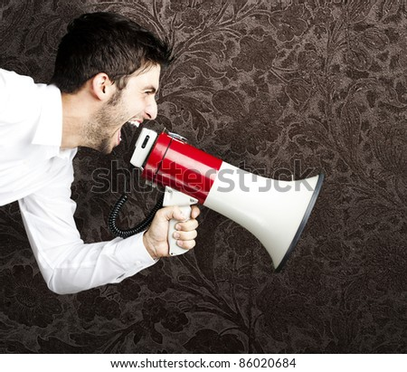 portrait of young man shouting using megaphone against a vintage wall - stock photo