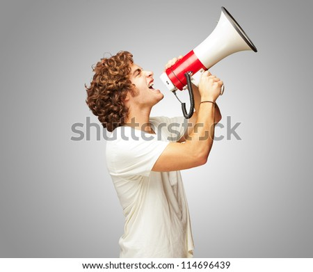 Portrait Of Young Man Shouting With A Megaphone Isolated On Gray Background - stock photo
