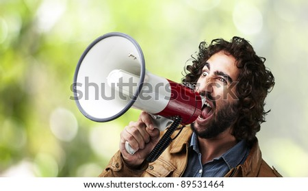 portrait of young man shouting with megaphone against a nature  background - stock photo